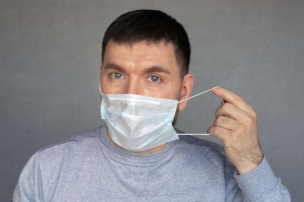 Il giovane mette sulla mascherina medica su fondo grigio cemento