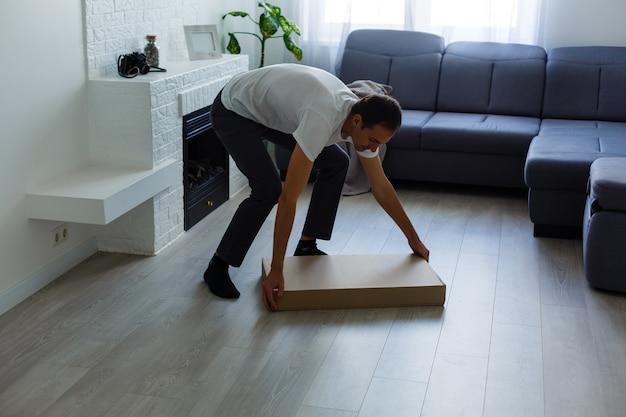 Giovane che mette mobili da assemblare mentre si trasferiscono nella tua nuova casa.