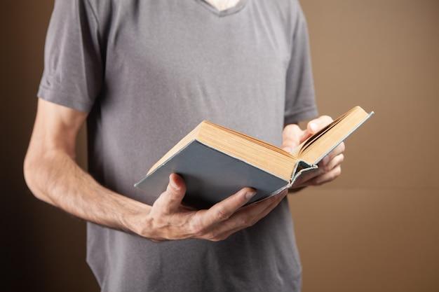 Giovane che legge un libro su sfondo marrone