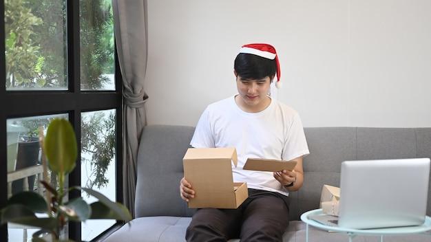 Giovane che legge una cartolina di natale da familiari e amici mentre apre i regali nel soggiorno.
