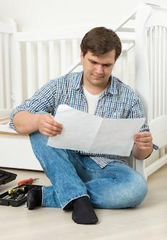 Giovane uomo che legge il manuale sull'assemblaggio della culla in legno