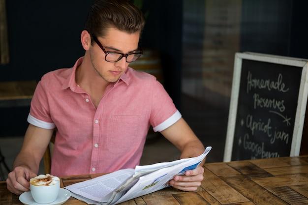 Giovane che legge il giornale mentre beve il caffè nella caffetteria