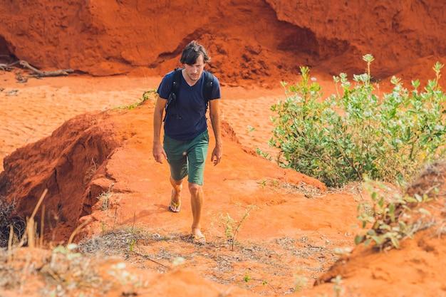 Giovane uomo nel canyon rosso vicino a mui ne, vietnam meridionale.