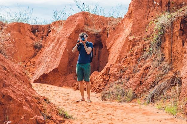 Giovane uomo nel canyon rosso vicino a mui ne, vietnam meridionale