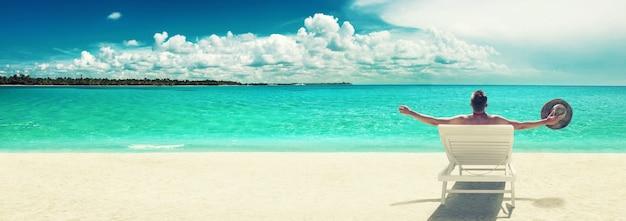 Giovane che si rilassa nella sedia a sdraio sulla spiaggia. sfondo vacanza.