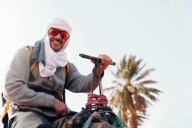 Giro del giovane sul dromedario nel deserto del sahara.