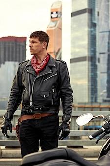 Giovane uomo in sella a una grande bici, motocicletta sulla strada della città contro la scena della costruzione urbana e cittadina