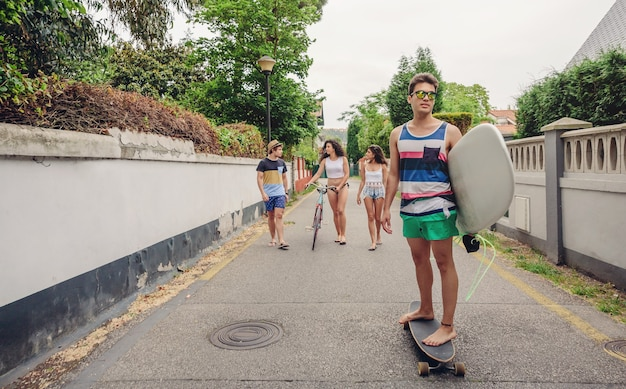 Giovane uomo in sella a skate e tenendo la tavola da surf con i suoi amici divertirsi in background in una giornata di sole. concetto di stile di vita estivo.
