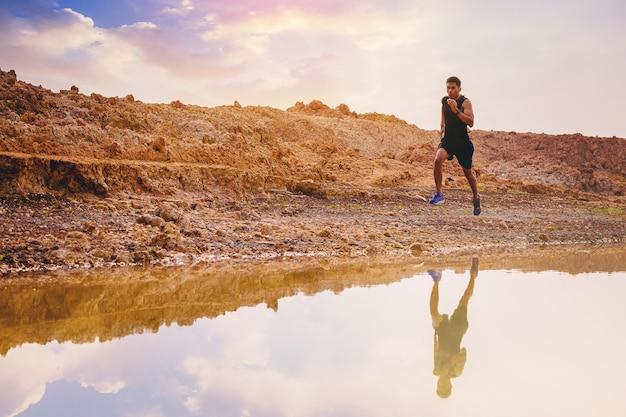 Giovane uomo runner in esecuzione sentiero sulla riva del lago di alba concetto sano e stile di vita healthy