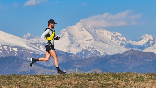 Giovane che corre su un prato di montagna