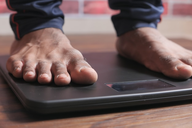 I piedi del giovane sulla scala del peso si chiudono