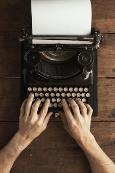 Mani del giovane che digitano su un'antica macchina da scrivere vintage