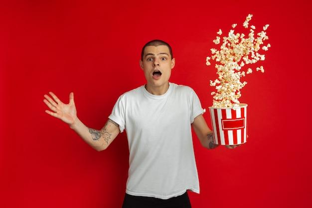 Ritratto di giovane uomo con popcorn sulla parete rossa dello studio