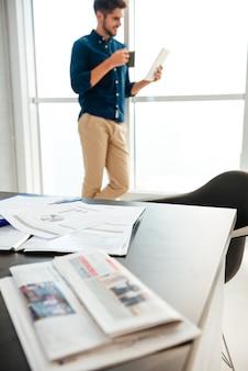 Tavolo del giovane con documenti e giornali e giovane uomo in piedi vicino alla finestra e bere il caffè durante la lettura del giornale