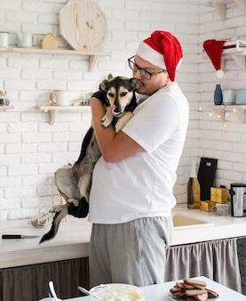 Giovane uomo in cappello della santa che tiene il suo cane tra le braccia in cucina