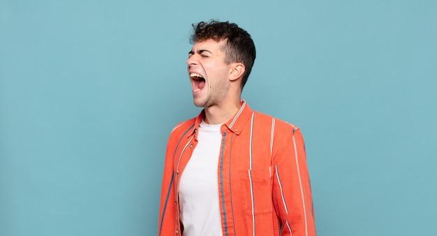 Giovane che urla furiosamente, urla in modo aggressivo, sembra stressato e arrabbiato
