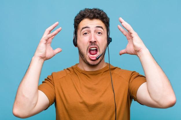 Giovane che urla con le mani in alto, sentendosi furioso, frustrato, stressato e sconvolto