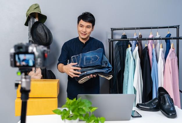 Giovane uomo che vende vestiti e accessori online tramite live streaming della telecamera. commercio elettronico online da casa