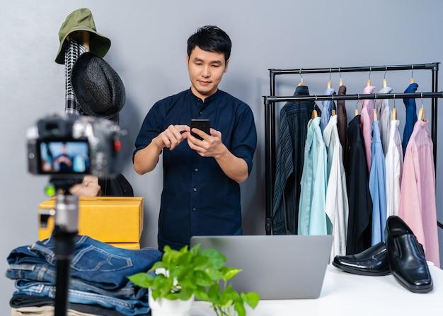 Giovane che vende vestiti e accessori online utilizzando lo smartphone e la fotocamera in live streaming. commercio elettronico online da casa
