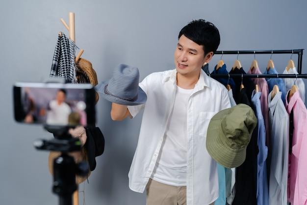 Giovane uomo che vende cappello e vestiti online tramite streaming live di smartphone. commercio elettronico online da casa