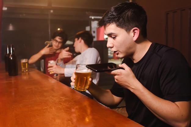 Un giovane che invia un audio vocale mentre beve birra con i suoi amici ubriachi al bar.