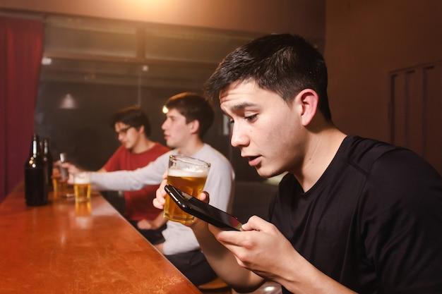 Un giovane invia una voce audio mentre beve una birra con i suoi amici al bar.