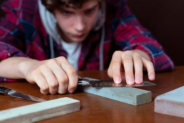 Giovane che affila un coltello sulla tavola di legno su fondo scuro b