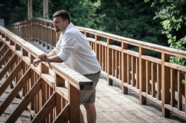 Un giovane in camicia si erge su un motu di legno nella foresta.