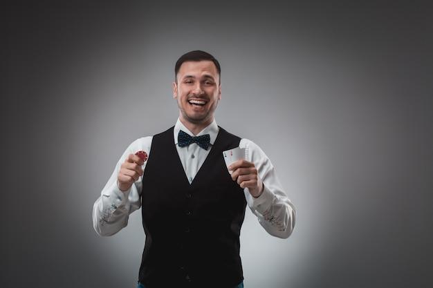 Il giovane in camicia e gilet mostra le sue carte e tiene in mano fiches da poker, foto in studio