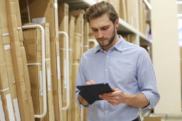 Giovane che fa shopping o lavora in un magazzino di ferramenta in piedi controllando le forniture sul suo tablet.