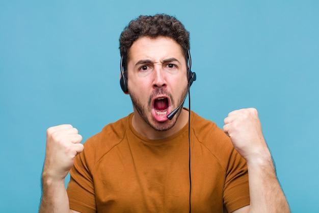 Giovane che grida in modo aggressivo con un'espressione arrabbiata o con i pugni chiusi per celebrare il successo