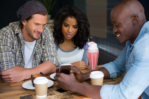 Giovane che mostra smart phone agli amici a tavola nella caffetteria