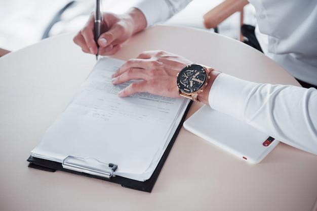 Il giovane firma i documenti in ufficio, vendite di successo.