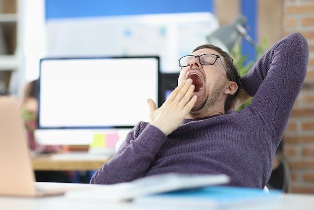 Ubicazione del giovane al tavolo in ufficio e che sbadiglia. concetto di procrastinazione