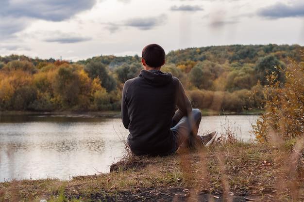 Un giovane uomo si siede sulla riva del fiume autunno nuvoloso sera. vista posteriore