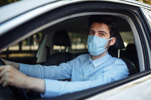 Il giovane si siede dietro il volante in macchina che indossa la mascherina medica sterile. distanza sociale, prevenzione della diffusione del virus e concetto di trattamento.