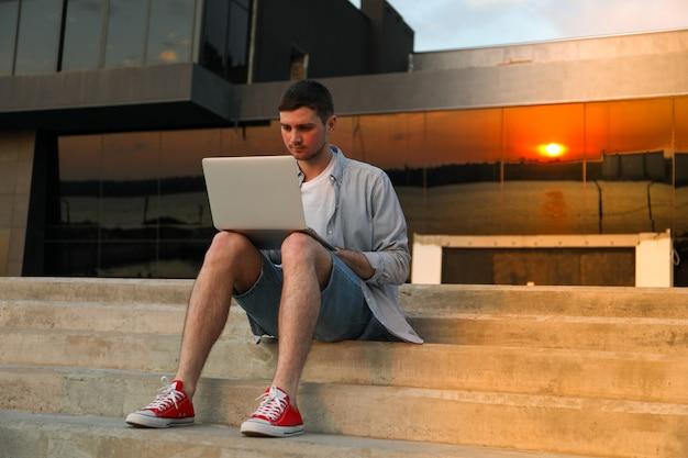 Il giovane si siede a passi e lavorando in un computer portatile all'aperto.