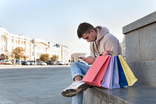 Il giovane si siede con il telefono in mano accanto a borse della spesa multicolori.