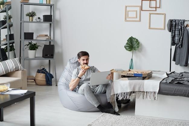 Giovane uomo seduto in un sacchetto di fagioli e mangiare la pizza mentre si guarda la serie online in quarantena