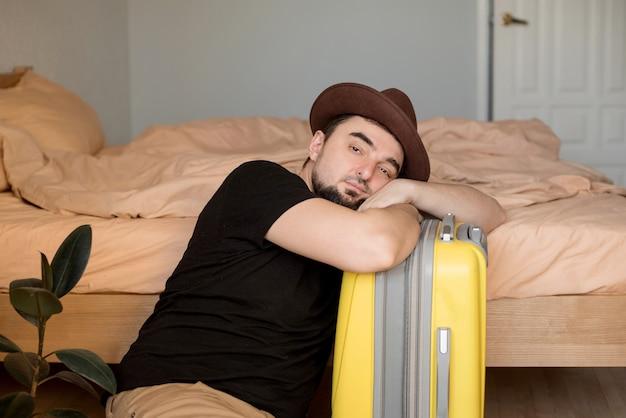 Giovane uomo seduto annoiato sulla valigia in attesa delle vacanze estive durante la stagione del coronavirus. concetto di blocco