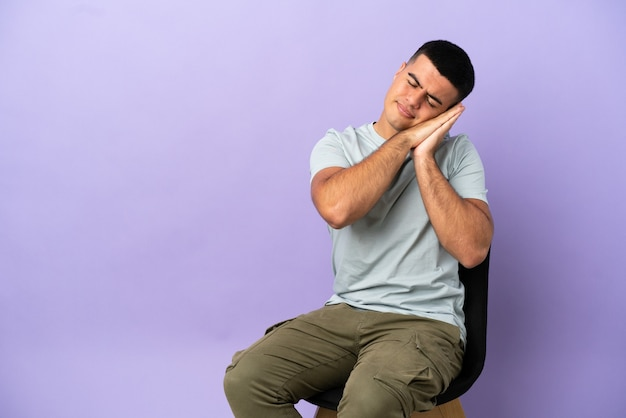 Giovane uomo seduto su una sedia su sfondo isolato facendo gesto di sonno in espressione adorabile