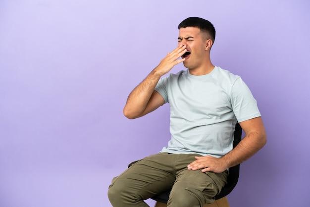 Giovane uomo seduto su una sedia su sfondo isolato che sbadiglia e copre la bocca spalancata con la mano