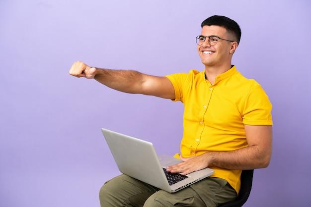 Giovane che si siede su una sedia con il computer portatile che dà un gesto di pollice in alto
