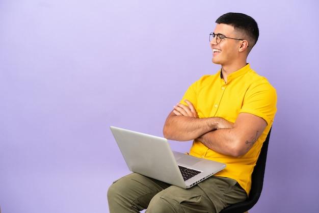 Giovane uomo seduto su una sedia con laptop felice e sorridente happy