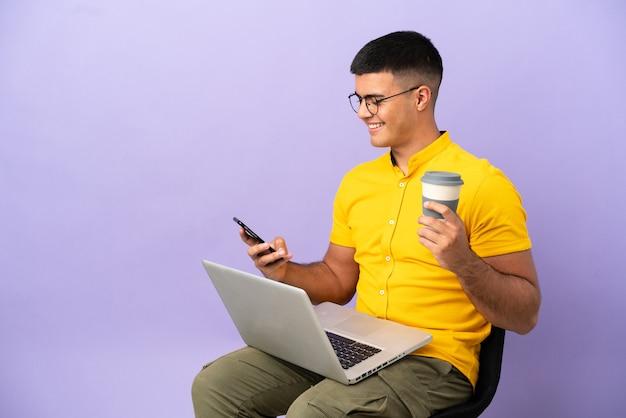 Giovane che si siede su una sedia con il computer portatile che tiene il caffè da portare via e un cellulare
