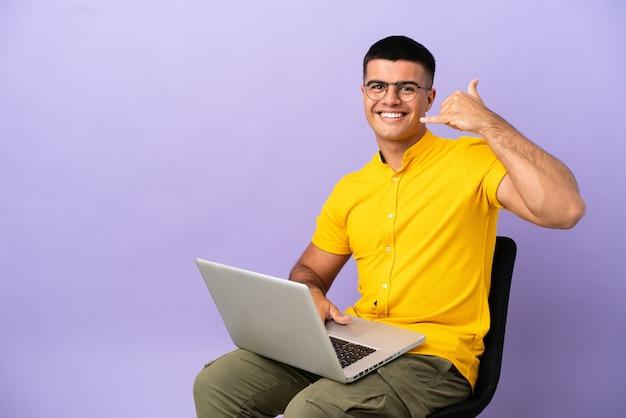 Giovane che si siede su una sedia con il computer portatile che fa il gesto del telefono. richiamami segno