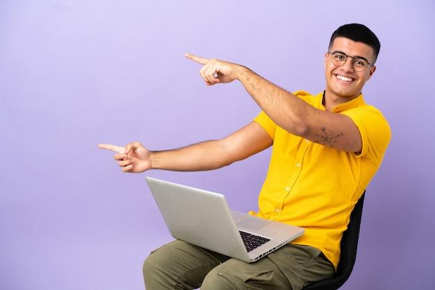 Giovane uomo seduto su una sedia con il computer portatile che punta il dito di lato e presenta un prodotto