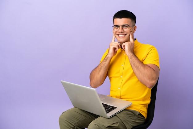 Giovane che si siede su una sedia con il computer portatile che sorride con un'espressione felice e piacevole