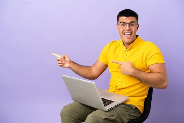 Giovane uomo seduto su una sedia con un laptop sorpreso e che indica il lato