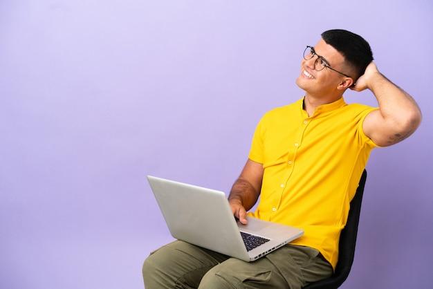 Giovane che si siede su una sedia con il computer portatile che pensa a un'idea